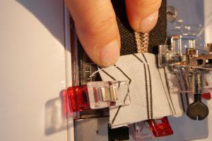 als Abschluss werden auf die Enden des Endlosreißverschlusses passende Stoffstreifen im Bruch genäht und die Enden somit verriegelt