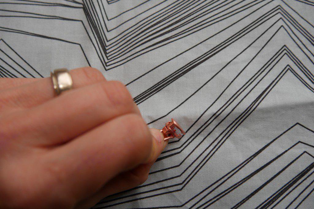 Zipper, Häkchen verhindert, dass sich der Schieber selbstständig in Öffnungsrichtung bewegt und der Reißverschluss sich selbstständig öffnet